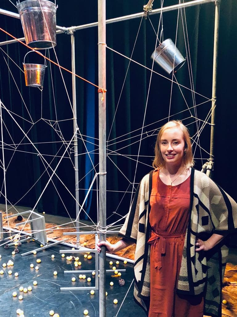 Image of producer Jo Walmsley, smiling, in orange dress, standing next to strings and buckets from the Tiger stage set.